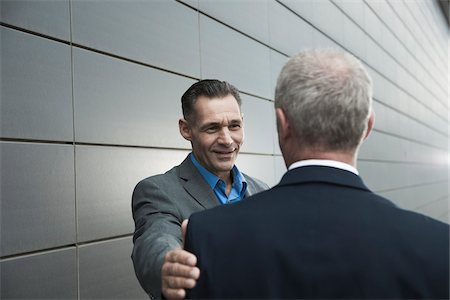 Mature businessmen standing in front of wall, talking Stock Photo - Premium Royalty-Free, Code: 600-06782198