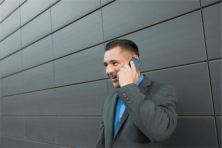 Close-up portrait of businessman standing in front of wall of building using cell phone, Mannheim, Germany Stock Photo - Premium Royalty-Free, Code: 600-06782190