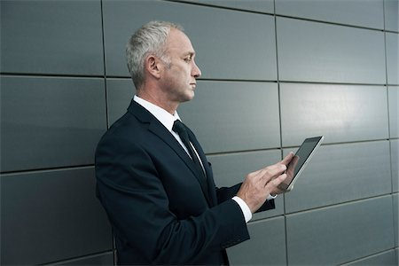 Mature businessman standing in front of wall, looking at tablet computer Stock Photo - Premium Royalty-Free, Code: 600-06782192