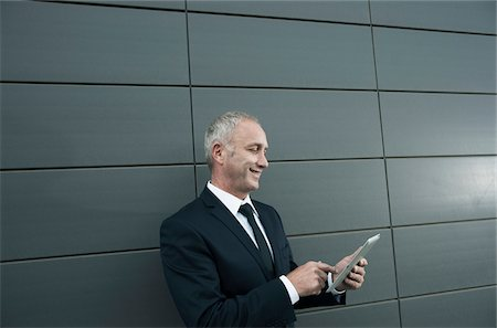 Mature businessman standing in front of wall, looking at tablet computer Stock Photo - Premium Royalty-Free, Code: 600-06782193