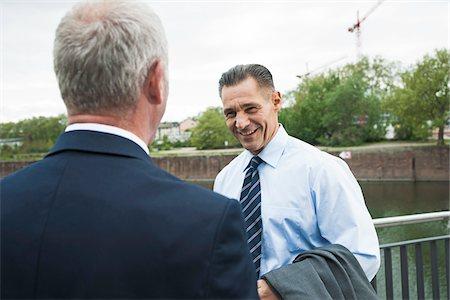 Mature businessmen standing by railing talking, Mannheim, Germany Stock Photo - Premium Royalty-Free, Code: 600-06782204