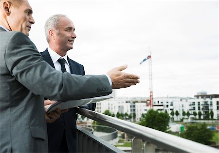 Mature businessmen standing on outdoor balcony, talking and overlooking city, Mannheim, Germany Stock Photo - Premium Royalty-Free, Code: 600-06782207