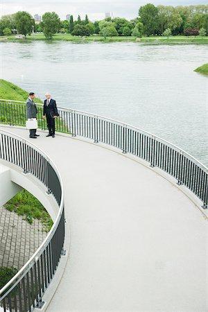 Mature businessmen standing on walkway talking, Mannheim, Germany Stock Photo - Premium Royalty-Free, Code: 600-06782208