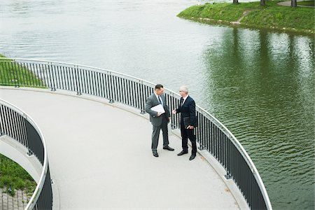 Mature businessmen standing on walkway talking, Mannheim, Germany Stock Photo - Premium Royalty-Free, Code: 600-06782209