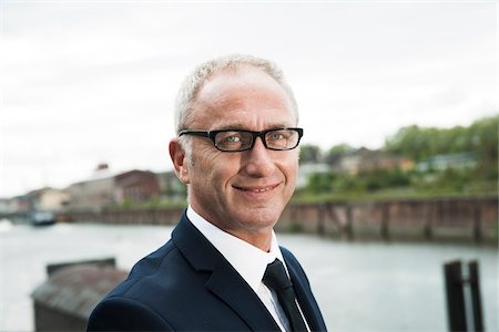portrait smile caucasian one - Portrait of mature businessman outdoors, wearing horn-rimmed eyeglasses, smiling at camera, Mannheim, Germany Stock Photo - Premium Royalty-Free, Code: 600-06782200