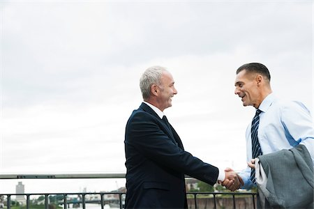Mature businessmen standing by railing, shaking hands outdoors, Mannheim, Germany Stock Photo - Premium Royalty-Free, Code: 600-06782202