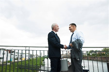 Mature businessmen standing by railing, shaking hands outdoors, Mannheim, Germany Stock Photo - Premium Royalty-Free, Code: 600-06782203