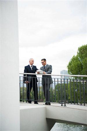 Mature businessmen standing on outdoor bridge talking, Mannheim, Germany Stock Photo - Premium Royalty-Free, Code: 600-06782214