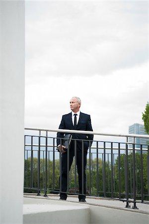 Mature businessman standing on bridge, Mannheim, Germany Stock Photo - Premium Royalty-Free, Code: 600-06782216