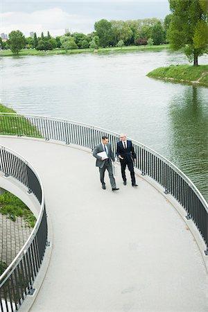 Mature businessmen on walkway talking, Mannheim, Germany Stock Photo - Premium Royalty-Free, Code: 600-06782210
