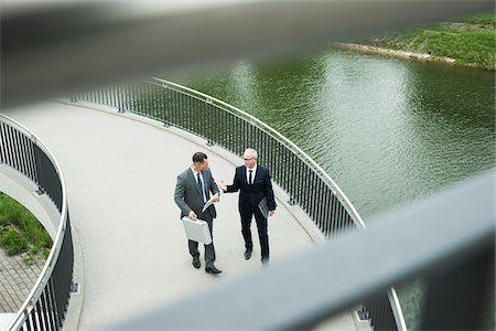 Mature businessmen on walkway talking, Mannheim, Germany Stock Photo - Premium Royalty-Free, Code: 600-06782213
