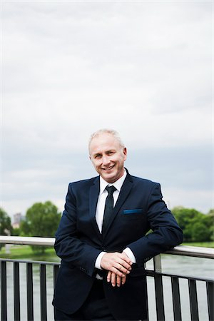 Portrait of mature businessman standing on bridge, smiling at camera and leaning on railing, Mannheim, Germany Stock Photo - Premium Royalty-Free, Code: 600-06782224