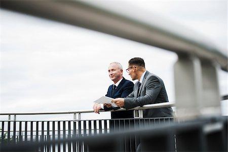 Mature businessmen standing on bridge talking, Mannheim, Germany Stock Photo - Premium Royalty-Free, Code: 600-06782225