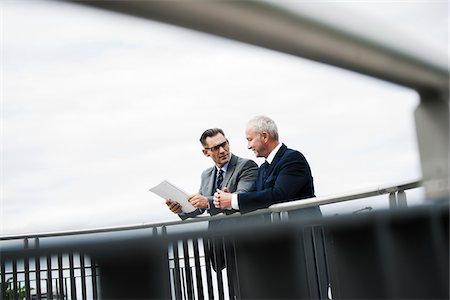 Mature businessmen standing on bridge talking, Mannheim, Germany Stock Photo - Premium Royalty-Free, Code: 600-06782226