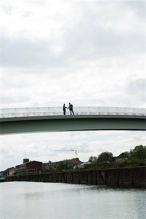 Silhouette of mature businessmen standing on bridge shaking hands, Mannheim, Germany Stock Photo - Premium Royalty-Free, Code: 600-06782229