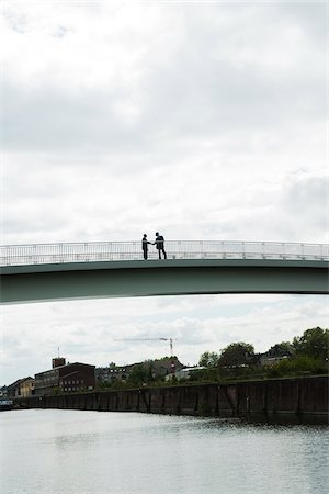 Silhouette of mature businessmen standing on bridge shaking hands, Mannheim, Germany Stock Photo - Premium Royalty-Free, Code: 600-06782229