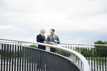 Mature businessmen standing on bridge talking, Mannheim, Germany Stock Photo - Premium Royalty-Free, Code: 600-06782221