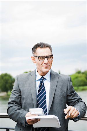 Portrait of mature businessman standing on bridge holding documents, wearing horn-rimmed eyeglasses, Mannheim, Germany Stock Photo - Premium Royalty-Free, Code: 600-06782223