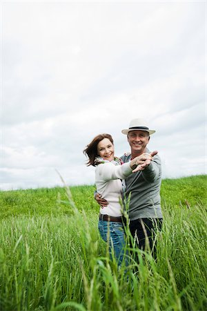 Mature couple dancing in field of grass, smiling at camera, Germany Stock Photo - Premium Royalty-Free, Code: 600-06782239