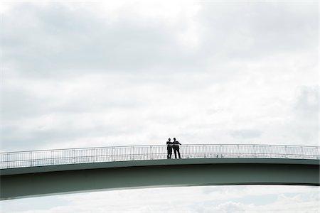 Silhouette of mature businessmen standing on bridge talking, Mannheim, Germany Stock Photo - Premium Royalty-Free, Code: 600-06782230