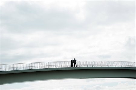 Silhouette of mature businessmen standing on bridge talking, Mannheim, Germany Stock Photo - Premium Royalty-Free, Code: 600-06782230
