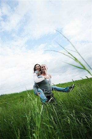 Mature couple in field of grass, man giving piggyback ride to woman, Germany Stock Photo - Premium Royalty-Free, Code: 600-06782246