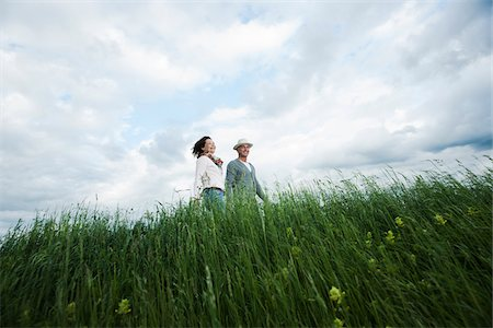 Mature couple walking in field of grass, Germany Stock Photo - Premium Royalty-Free, Code: 600-06782249