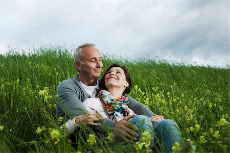 Mature couple sitting in field of grass, embracing, Germany Stock Photo - Premium Royalty-Free, Code: 600-06782254