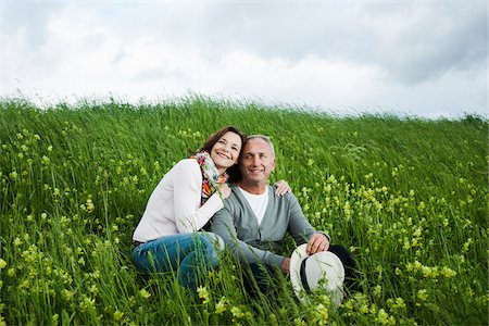 portrait looking away - Portrait of mature couple sitting in field of grass, embracing, Germany Stock Photo - Premium Royalty-Free, Code: 600-06782251