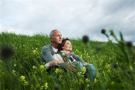 Mature couple sitting in field of grass, embracing, Germany Stock Photo - Premium Royalty-Free, Code: 600-06782253