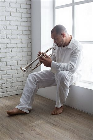 Portrait of Musician Playing Trumpet by Window, Italy Stock Photo - Premium Royalty-Free, Code: 600-06803959