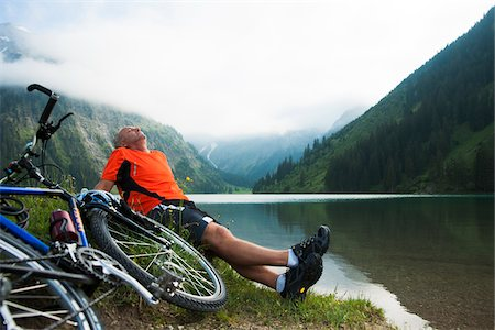 Mature Man Sitting by Lake with Mountain Bike, Vilsalpsee, Tannheim Valley, Tyrol, Austria Stock Photo - Premium Royalty-Free, Code: 600-06819404