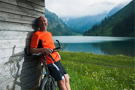 people mountain biking - Mature Man leaning against Wooden Building with Mountain Bike, Vilsalpsee, Tannheim Valley, Tyrol, Austria Stock Photo - Premium Royalty-Free, Code: 600-06819414
