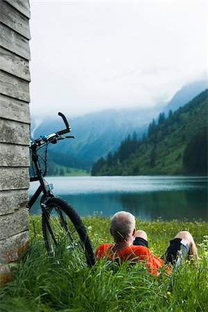 Mature Man with Mountain Bike Relaxing by Lake, Vilsalpsee, Tannheim Valley, Tyrol, Austria Stock Photo - Premium Royalty-Free, Code: 600-06819419