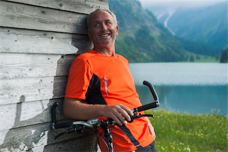 people mountain biking - Mature Man leaning against Wooden Building with Mountain Bike, Vilsalpsee, Tannheim Valley, Tyrol, Austria Stock Photo - Premium Royalty-Free, Code: 600-06819413