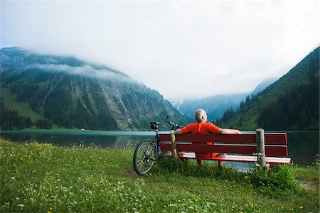 people sitting on bench - Mature Man on Bench by Lake with Mountain Bike, Vilsalpsee, Tannheim Valley, Tyrol, Austria Stock Photo - Premium Royalty-Free, Code: 600-06819424