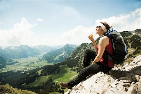 Mature woman sitting on cliff, hiking in mountains, Tannheim Valley, Austria Stock Photo - Premium Royalty-Free, Code: 600-06826341