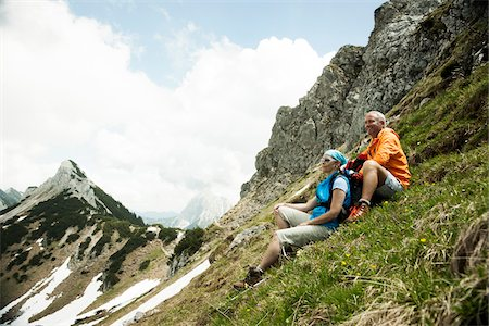 Mature couple sitting on grass, hiking in mountains, Tannheim Valley, Austria Stock Photo - Premium Royalty-Free, Code: 600-06826369