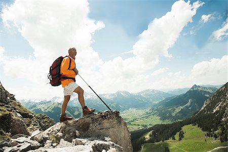 Mature man standing on cliff, hiking in mountains, Tannheim Valley, Austria Stock Photo - Premium Royalty-Free, Code: 600-06826375