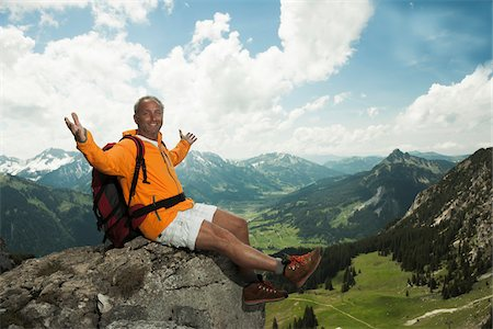 Mature man sitting on cliff with arms raised in air, hiking in mountains, Tannheim Valley, Austria Stock Photo - Premium Royalty-Free, Code: 600-06826376