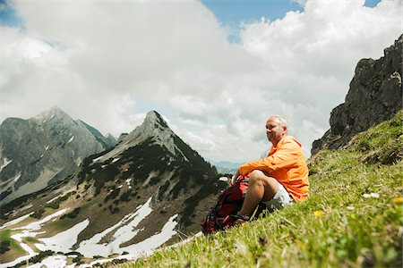 Mature man sitting on grass, hiking in mountains, Tannheim Valley, Austria Stock Photo - Premium Royalty-Free, Code: 600-06826370