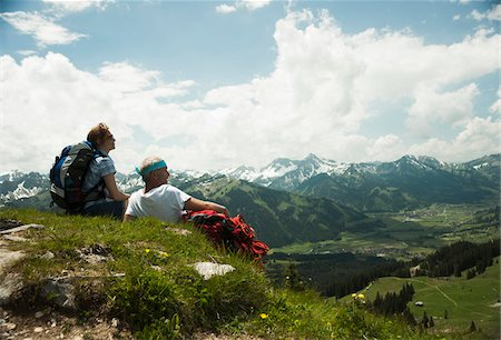Backview of mature couple sitting on grass, hiking in mountains, Tannheim Valley, Austria Stock Photo - Premium Royalty-Free, Code: 600-06826386