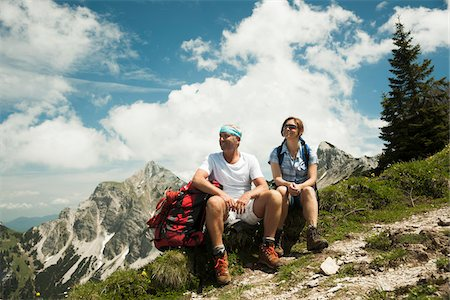 Mature couple sitting on grass, hiking in mountains, Tannheim Valley, Austria Stock Photo - Premium Royalty-Free, Code: 600-06826388
