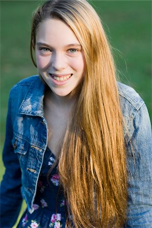 Portrait of pre-teen girl with long, blond hair, wearing jean jacket, outdoors Stock Photo - Premium Royalty-Free, Code: 600-06847436