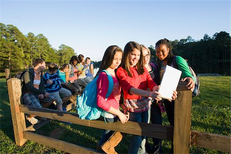 Group of pre-teens sitting on fence, looking at tablet computer and cellphones, outdoors Stock Photo - Premium Royalty-Free, Code: 600-06847446