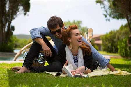 Young couple lying on grass reading book during summer holidays, Sardinia, Italy Stock Photo - Premium Royalty-Free, Code: 600-06841647