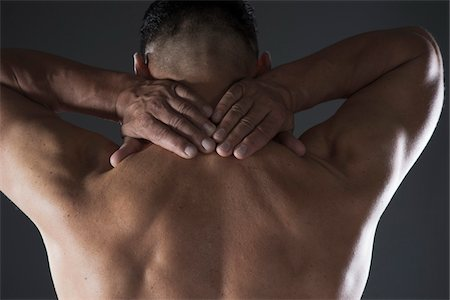 Close-up of Man with Hands on Back of his Neck, Studio Shot Stock Photo - Premium Royalty-Free, Code: 600-06841744