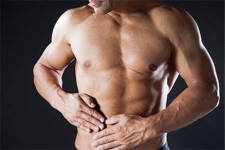 Close-up of Muscular Man with Hands on Stomach, Studio Shot Stock Photo - Premium Royalty-Free, Code: 600-06841747