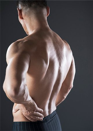 Muscular Man with Hand on Lower Back, Studio Shot Stock Photo - Premium Royalty-Free, Code: 600-06841767