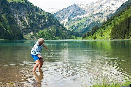 Mature man skipping stones at Lake Vilsalpsee, Tannheim Valley, Austria Stock Photo - Premium Royalty-Free, Code: 600-06841889